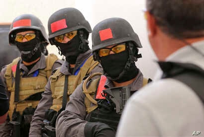 FILE - Members of a Tunisian police commando unit listen to instructions during a drill at the Jordan Gendarmerie Training Academy, in al-Swaqa, about 44 miles (70 kilometers) south of Amman, Jordan, March 18, 2018. The U.S.-funded center conducts co...