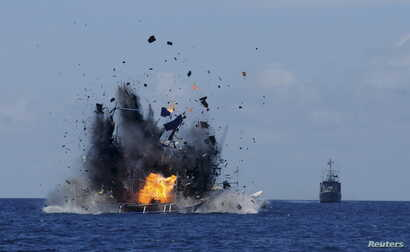 The Indonesian navy scuttles foreign fishing vessels caught fishing illegally in Indonesian waters near Bitung, North Sulawesi, May 20, 2015. A total of 19 foreign boats from Vietnam, Thailand, Philippines and one from China were destroyed as part of...