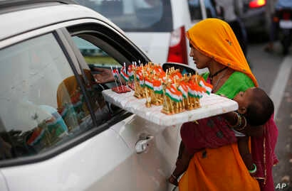 A woman sells Indian national flag memorabilia on the eve of Independence Day in Lucknow, India, Tuesday, Aug. 14, 2018.
