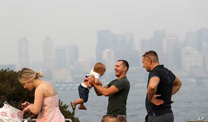 A man twirls a young child on a waterfront park as downtown Seattle disappears in a smoky haze behind, Aug. 19, 2018.