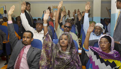 Somalia lawmakers raise their hands during a confidence vote on Prime Minister Abdiweli Sheikh Ahmed, at the Parliament Building in Mogadishu, Somalia, Dec. 6, 2014.