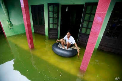 Nguyen Van Bon paddles a rubber tire tube at his flooded house in Chuong My district, Hanoi, Vietnam, July 31, 2018.