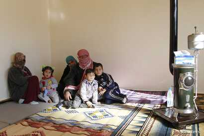 Syrian refugees, who fled the violence in the Syrian town of Qusair, sit at a temporary home, in the hillside town of Arsal in Lebanon's Bekaa Valley, March 5, 2012.
