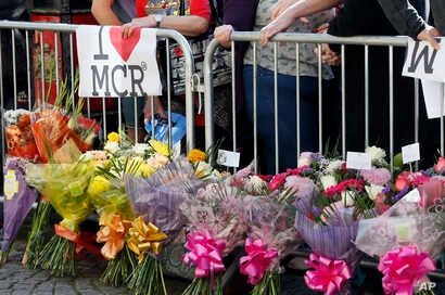 People attend a vigil in Albert Square, Manchester, England, May 23, 2017, the day after the suicide attack at an Ariana Grande concert that left 22 people dead as it ended Monday night.