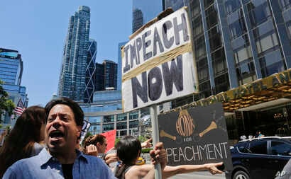 Protesters rally outside a Trump hotel to call for the impeachment of President Trump, July 2, 2017, in New York.