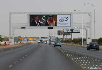 U.S. President Donald Trump's and Saudi Arabia's King's Salman bin Abdulaziz Al Saud's photos are seen with flags of both countries on airport road as part of celebrations to welcome United States President Donald Trump, in Riyadh, Saudi Arabia, May ...
