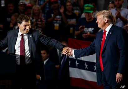 12th Congressional District Republican candidate Troy Balderson (L) reaches for President Donald Trump as he speaks at a rally at Olentangy Orange High School in Lewis Center, Ohio, Aug. 4, 2018.