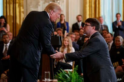 President Donald Trump shakes hands with acting Department of Veterans Affairs Secretary Robert Wilkie after announcing he will nominate him to lead the department during an event on prison reform in the East Room of the White House, May 18, 2018, in...