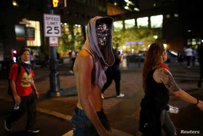 A masked demonstrator walks the streets of downtown past midnight as people protest the police shooting of Keith Scott in Charlotte, North Carolina, U.S., September 23, 2016.