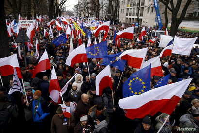 People hold European Union and Polish national flags during an anti-government demonstration in front of the Constitutional Court in Warsaw, Poland, Dec. 12, 2015.