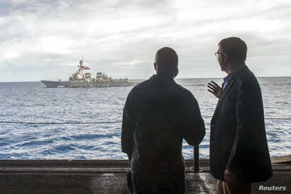 FILE - U.S. Secretary of Defense Ash Carter (R) speaks with U.S. Navy Cmdr. Robert C. Francis Jr., as Carter and Malaysian Defense Minister  Hishammuddin Hussein (Not Pictured) visited the USS Theodore Roosevelt aircraft carrier in the South China Se...