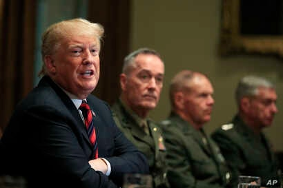 President Donald Trump, with Joint Chiefs Chairman Gen. Joseph Dunford and Marine Corps Commandant Gen. Robert Neller, speaks during a briefing with senior military leaders in the Cabinet Room at the White House in Washington, Oct. 23, 2018.
