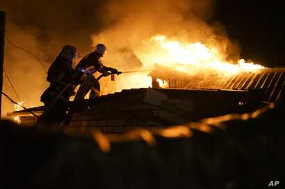 Firefighters extinguish fire at a house destroyed by night-long shelling in Donetsk, eastern Ukraine, Aug. 16, 2015.