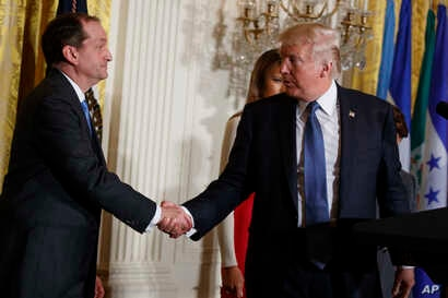 President Donald Trump shakes hands with Secretary of Labor Alex Acosta during a Hispanic Heritage Month event in the East Room of the White House, Oct. 6, 2017, in Washington.