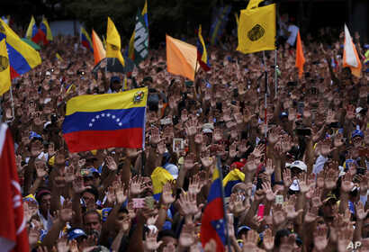 Anti-government protesters hold their hands up during the symbolic swearing-in of Juan Guaido, head of the opposition-run congress who declared himself interim president of Venezuela during a rally demanding President Nicolas Maduro's resignation in ...