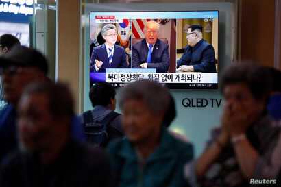 People watch a TV broadcasting a news report on the upcoming dismantling of the Punggye-ri nuclear testing site, in Seoul, South Korea, May 23, 2018.