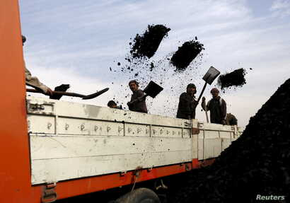 FILE - Laborers unload coal from a truck at a coal dump site in Kabul, Afghanistan, Nov. 19, 2015.