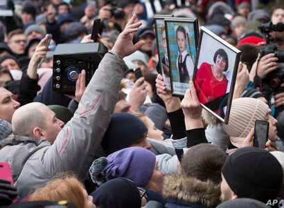 People hold portraits of relatives as they gather to remember the victims of a fire in a multi-story shopping center in the Siberian city of Kemerovo, about 3,000 kilometers (1,900 miles) east of Moscow, Russia, March 27, 2018.