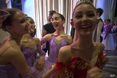 Harper Ortlieb, center, from Mount Hood, Oregon, and her ballet school colleagues congratulate each other after performing at the Bolshoi Ballet Academy in Moscow, March 3, 2016.