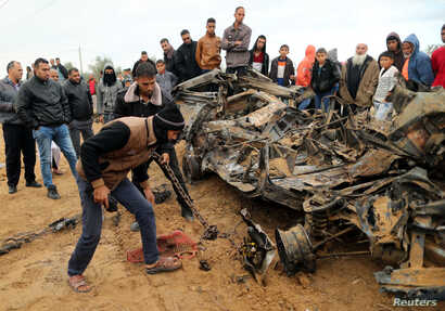 Palestinians inspect the remains of a vehicle that was destroyed in an Israeli air strike, in Khan Younis in the southern Gaza Strip,  Nov. 12, 2018.