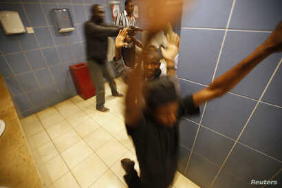 Armed police search customers taking cover inside a bathroom while combing through the Westgate shopping center for gunmen in Nairobi, Sept. 21, 2013.