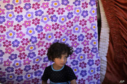 A Syrian girl, who fled her home with her family due to fighting between the Syrian army and the rebels, takes refuge at the Bab Al-Salameh border crossing, near the Syrian town of Azaz, Aug. 23, 2012.