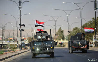 Iraqi security forces advance in military vehicles in Kirkuk, Iraq, Oct. 16, 2017.