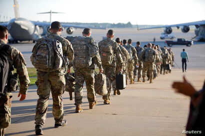 Soldiers of the 602nd Area Medical Support Company walk out to their C-17 transport plane on Pope Army Airfield as they are deployed to St. Thomas in the U.S. Virgin Islands to aid in the aftermath of Hurricane Irma, at Fort Bragg, N.C., Sept. 13, 20...