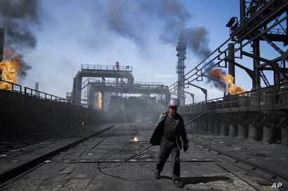 FILE - A worker carries a metal rod at the frontline Avdiivka coking plant in eastern Ukraine, Aug. 4, 2015.