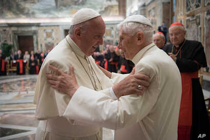Pope Francis, left, and retired Pope Benedict XVI embrace during a ceremony to celebrate Benedict's 65th anniversary of his ordination as a priest, in the Clementine Hall of the Apostolic Palace, at the Vatican, June 28, 2016.