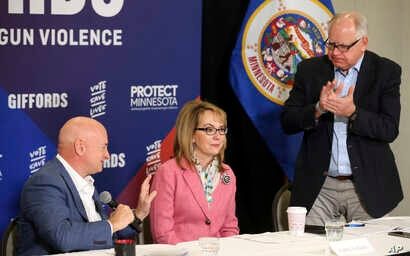 Minnesota gubernatorial candidate, Democrat Tim Walz, right, applauds as Capt. Mark Kelly, left, introduces his wife, former Rep. Gabby Giffords as they hosted a roundtable against gun violence in Minneapolis, Oct. 26, 2018. The 2018 election marks ...