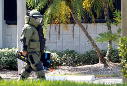 A member of the Broward County Sheriff's Office bomb squad walks to the building where U.S. Rep. Debbie Wasserman Schultz's office is housed in Sunrise, Florida, Oct. 24, 2018.