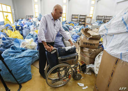 Ramadan Ghazawi, a Palestinian official at the post office in the West Bank city of Jericho, stands next to a folded wheelchair, one of many items of previously undelivered mail in Jericho on Aug. 14, 2018.