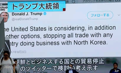 FILE - People walk by a TV news program showing a tweet,  issued by U.S. President Donald Trump, during a report on a North Korean nuclear test, in Tokyo, Sept. 4, 2017.