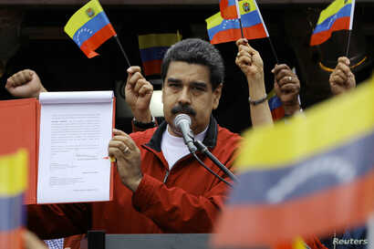 "Venezuela's President Nicolas Maduro shows a document with the details of a ""constituent assembly"" to reform the constitution during a rally at Miraflores Palace in Caracas, Venezuela, May 23, 2017."