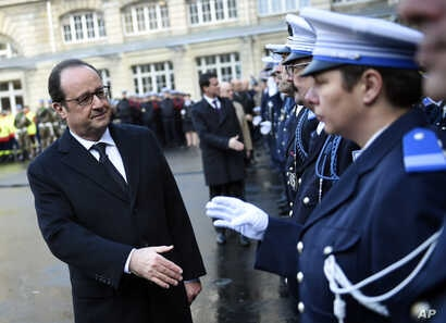 French President Francois Hollande shakes hands to police officers at the Paris' police headquarters, Jan. 7, 2016, one year after the attack targeting the French satirical newspaper Charlie Hebdo.