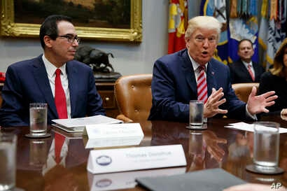 Treasury Secretary Steve Mnuchin listens as President Donald Trump speaks during a meeting on tax policy with business leaders in the Roosevelt Room of the White House, Tuesday, Oct. 31, 2017, in Washington.