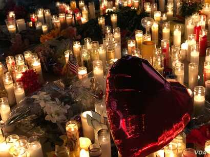 A red heart-shaped balloon flies over lit candles honoring the victims of the Las Vegas shooting, Oct. 2, 2017. (Photo: S. Dizayee / VOA Turkish Service)