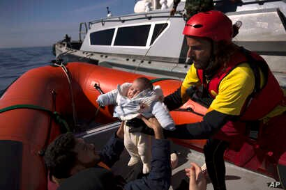 FILE - A 2-month-old baby from Libya is taken from a Libyan coast guard ship and loaded into a rubber rescue craft by members of the Spanish NGO Proactiva Open Arms, after being rescued from a wooden boat sailing out of control in the Mediterranean S...