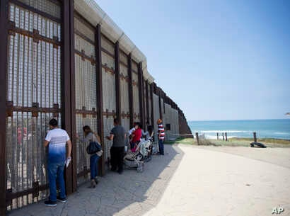 n this May 1, 2016 picture, Eva Lara, second from let, reacts as she reaches for her grandmother Juana Lara through the border wall during a brief visitation near where Mexico and the United States meet at the Pacific Ocean in San Diego.