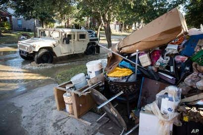 A military vehicle passes flood-damaged belongings piled on a homeowners' front lawn in the aftermath of Hurricane Harvey at the Canyon Gate community in Katy, Texas, Sept. 7, 2017.