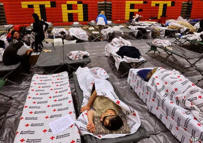 Evacuees from a wildfire rest on cots and blanket supplied by the Red Cross in the gymnasium at Taft Charter High School in the Woodland Hills section of Los Angeles on Nov. 9, 2018.