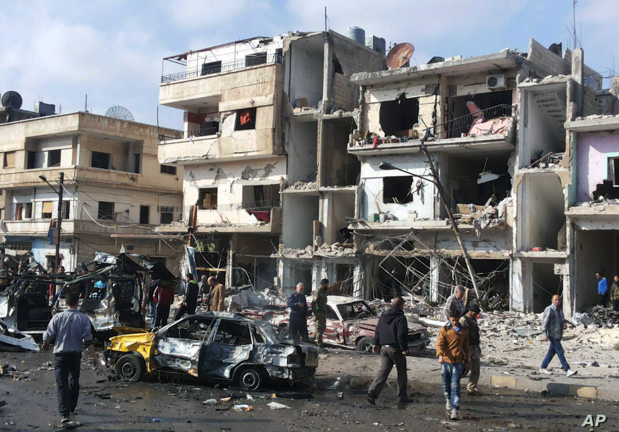 Syrian citizens gather at the scene where two blasts exploded in the pro-government neighborhood of Zahraa, in Homs province, Syria, Feb. 21, 2016. The Islamic State group claimed responsibility for this and another attack Sunday.