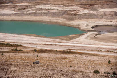 FILE - A partial view of Lar dam's reservoir at Damavand, 70 kilometers northeast of Tehran. Authorities warned Tehran residents to drastically reduce their water consumption, as three of the five dams supplying the capital are almost empty, Sept. 17...