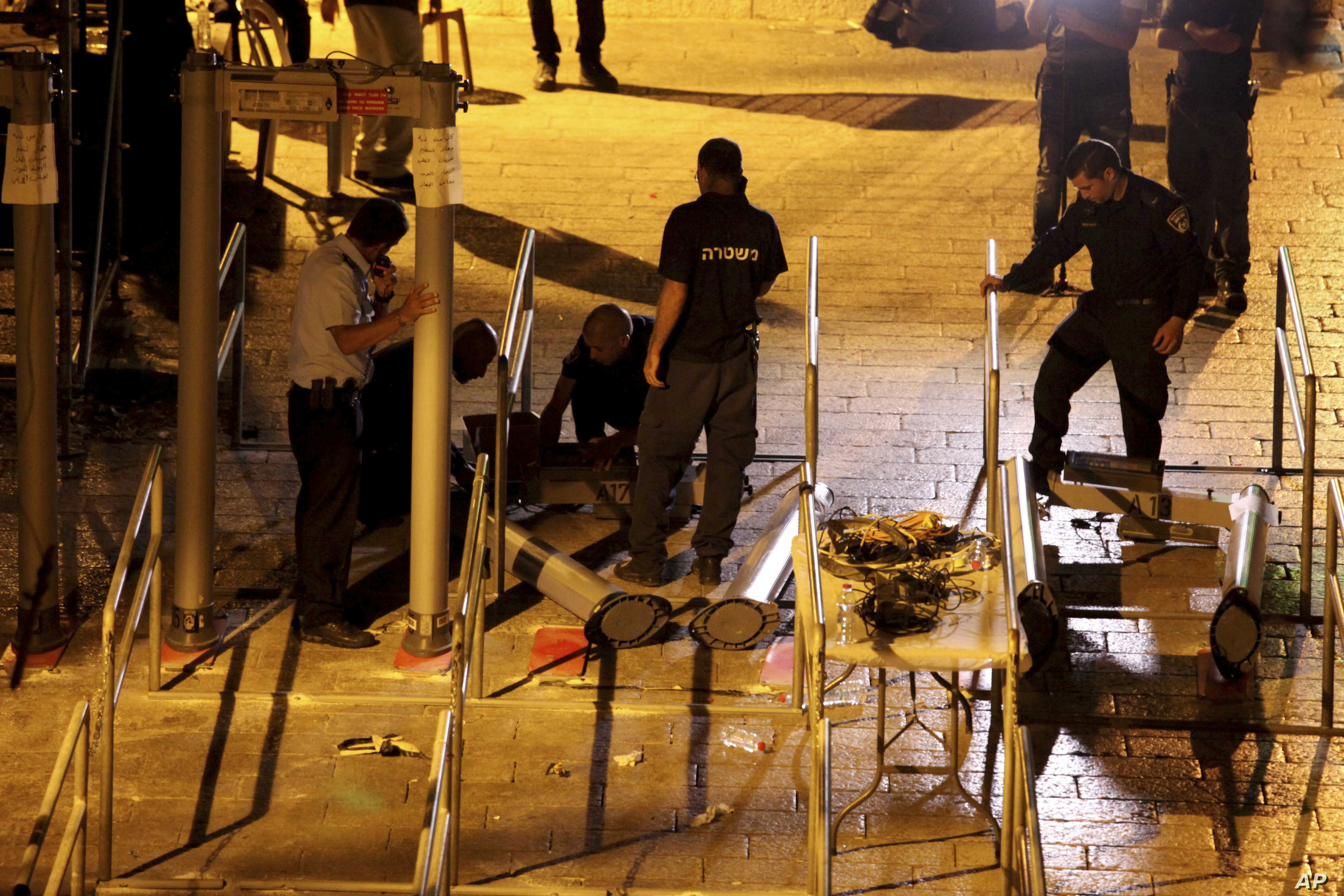 Israeli police officers dismantle metal detectors outside the al-Aqsa Mosque compound in Jerusalem's Old City, July 25, 2017.