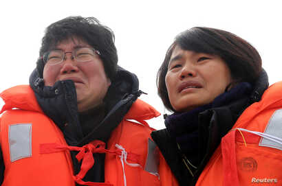 Family members of victims onboard the sunken ferry Sewol react as they look on during its salvage operations at the sea off Jindo, South Korea,  March 26, 2017.