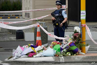 Police stand by a collection of flowers near the Linwood mosque in Christchurch, New Zealand, March 16, 2019, where one of the two mass shootings occurred.