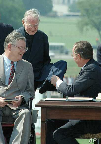 The Rev. Harold H. Wilke, top left, accepts a pen from President George Bush with his left foot, after Bush signed into law the Americans with Disabilities Act of 1990 at a White House South Lawn ceremony July 26, 1990. Wilke, who was born without ar...