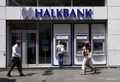 A customer uses an automated teller machine at a branch of Halkbank in Istanbul, Aug. 15, 2014.