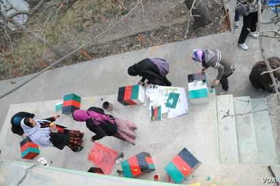 A group of women painting the memory boxes in Kabul, Afghanistan. (Photo: Afghanistan Human Rights and Democracy Organization)